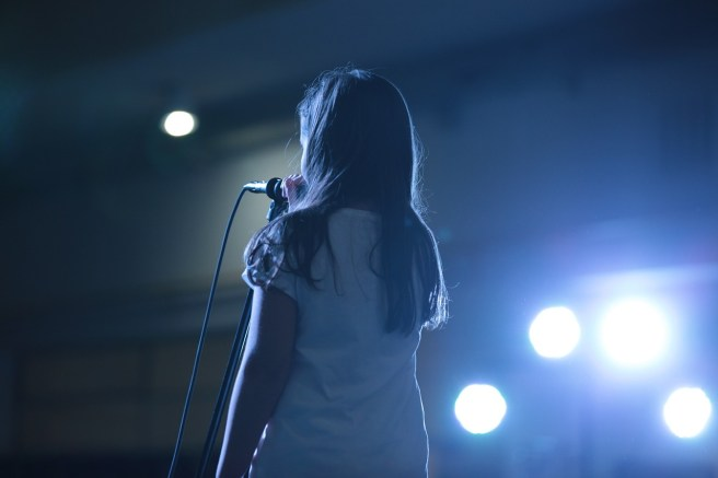 girl using her voice on stage
