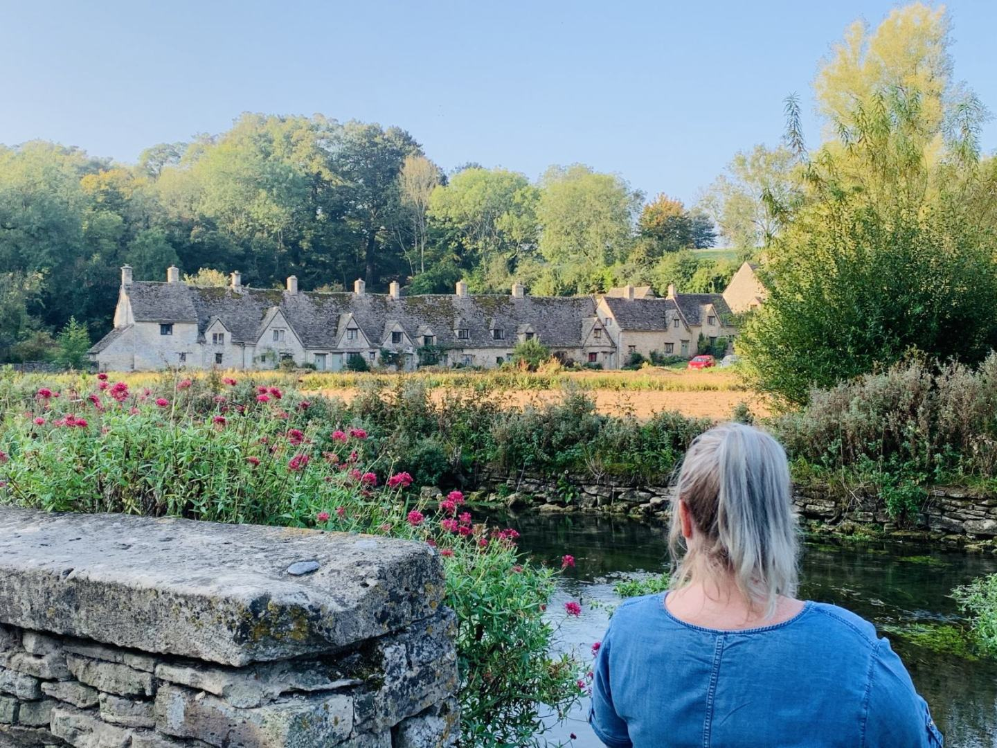Kerry is sitting by the river, looking out towards a beautiful row of old cottages. places to visit Cotswolds