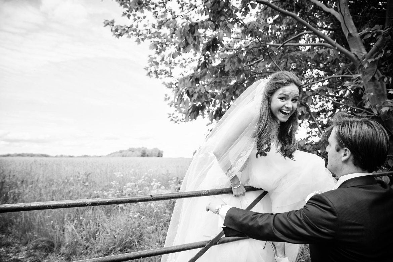 bride climbs over gate