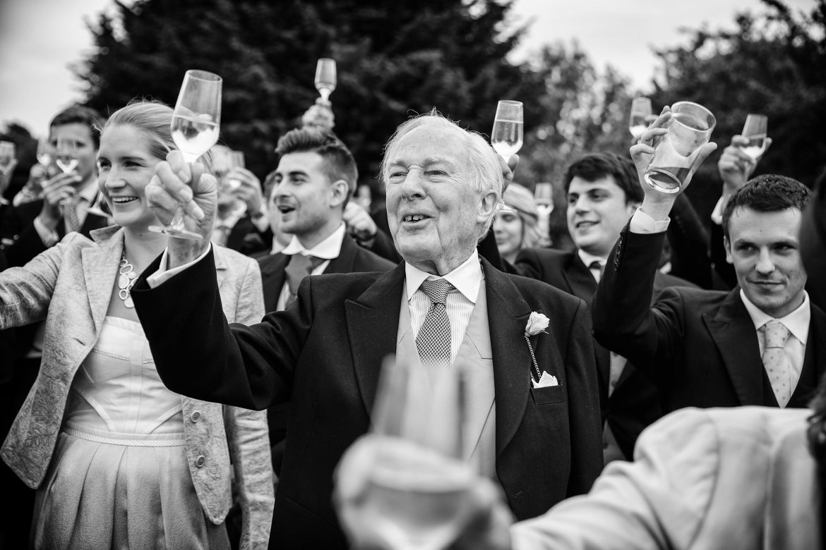 black and white photograph of guests toasting at wedding