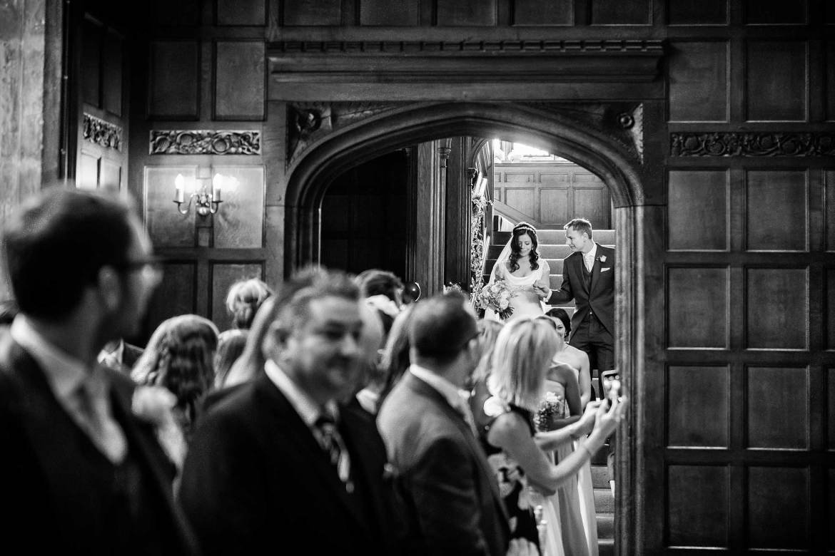 Amy and her Dad make their way down the stairs in Hengrave Hall. the image is black and white.