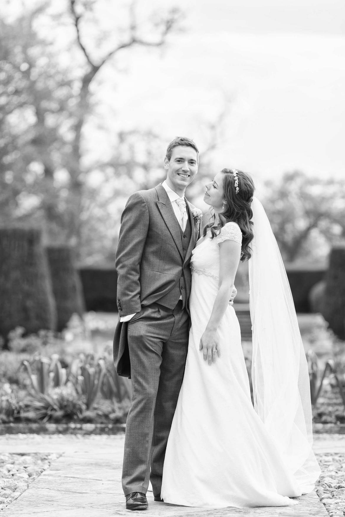Black and white picture of Amy and Jack looking at each at their Hengrave Hall Wedding