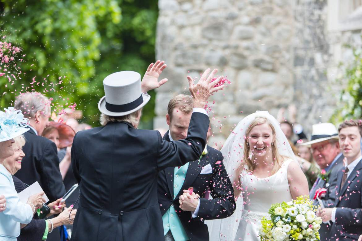The groom father throws confetti outside All Saints Fulham