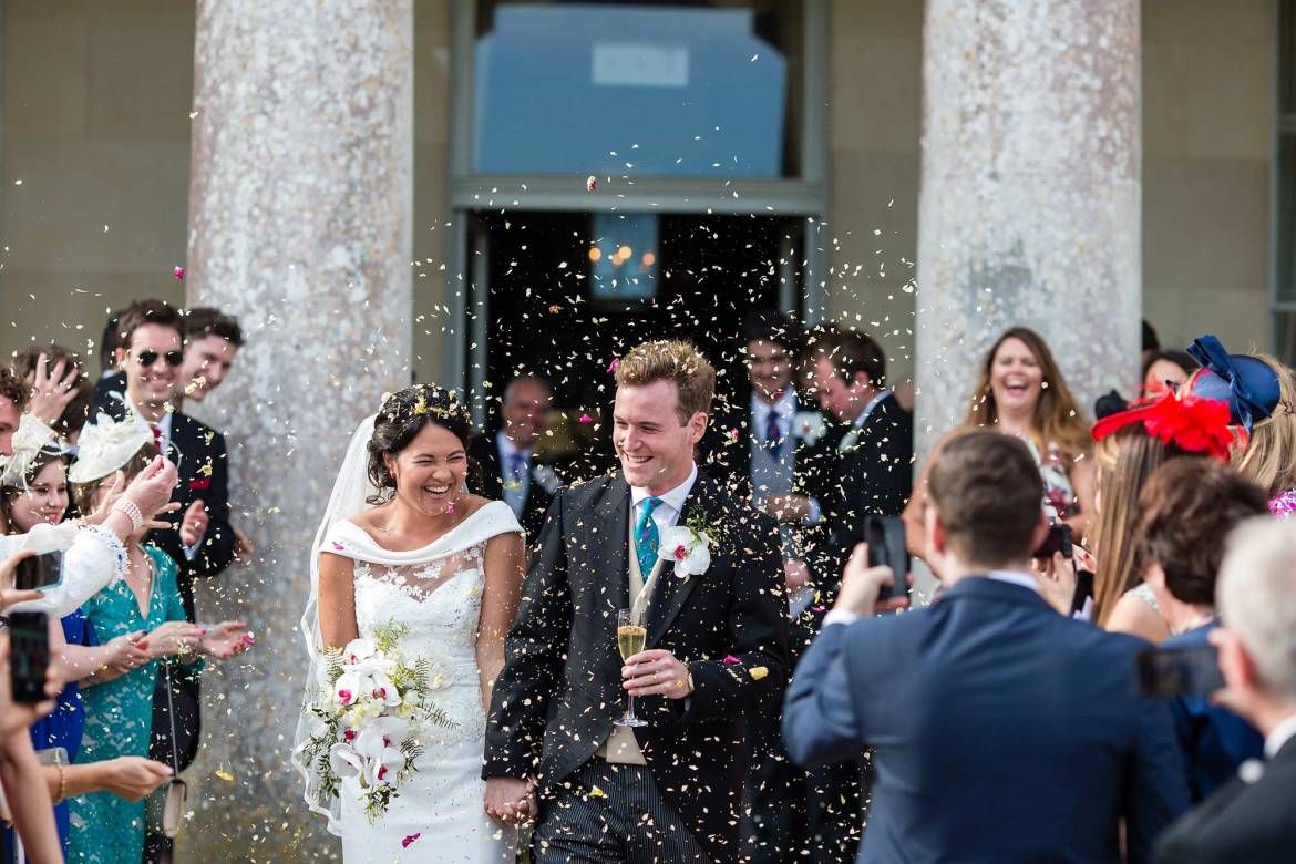 The guest shower the couple with confetti after their wedding at goodwood house