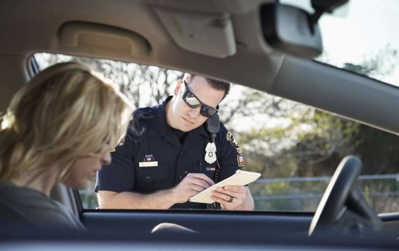 Police officer giving woman a traffic ticket.