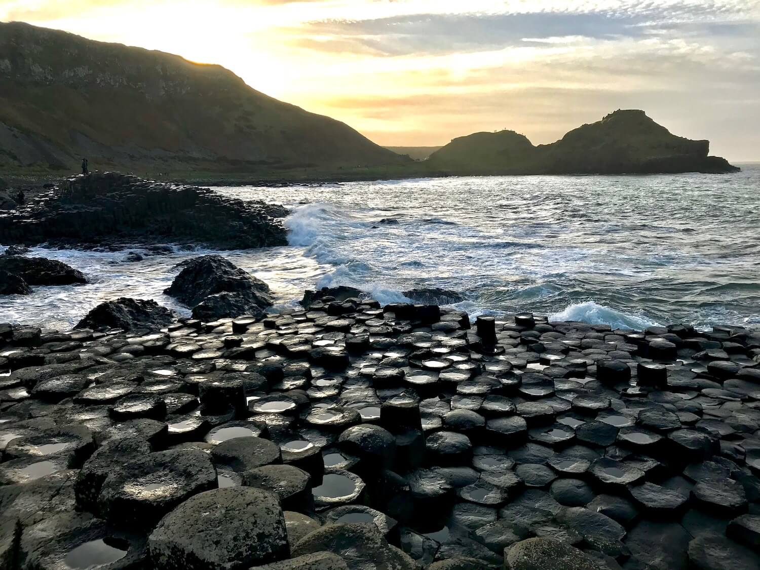 The Giant's Causeway is an area of about 40,000 interlocking basalt columns which are shown in the foreground of this photo. Dramatic high cliffs leading to the sea are in the background with blue sky.