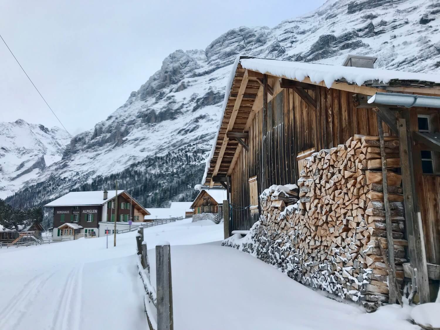 Walking up upon a Swiss barn with stacked wood pile and a mountainside restaurant inn in the far distance. All under the rocky peak of Eiger.