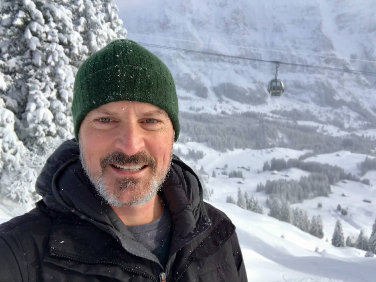 Close of selfie shot of Matthew Kessi with a ski gondola moving in the background. There are snow covered trees and a valley below in the background with snow covered Swiss chalets and the base of another rocky Alpine peak.