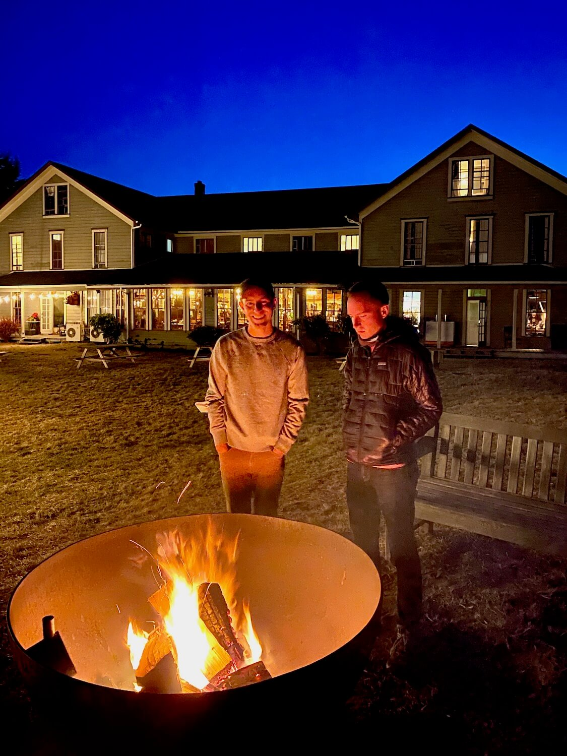 Two men stand beside a fire pit in front of a historic looking wood framed hotel. The fire is bright and crackling yellow and reflects on the faces of the two men. In the background, the hotel commands the skyline, ablaze with lights shining from within all under a blue dusk sky.
