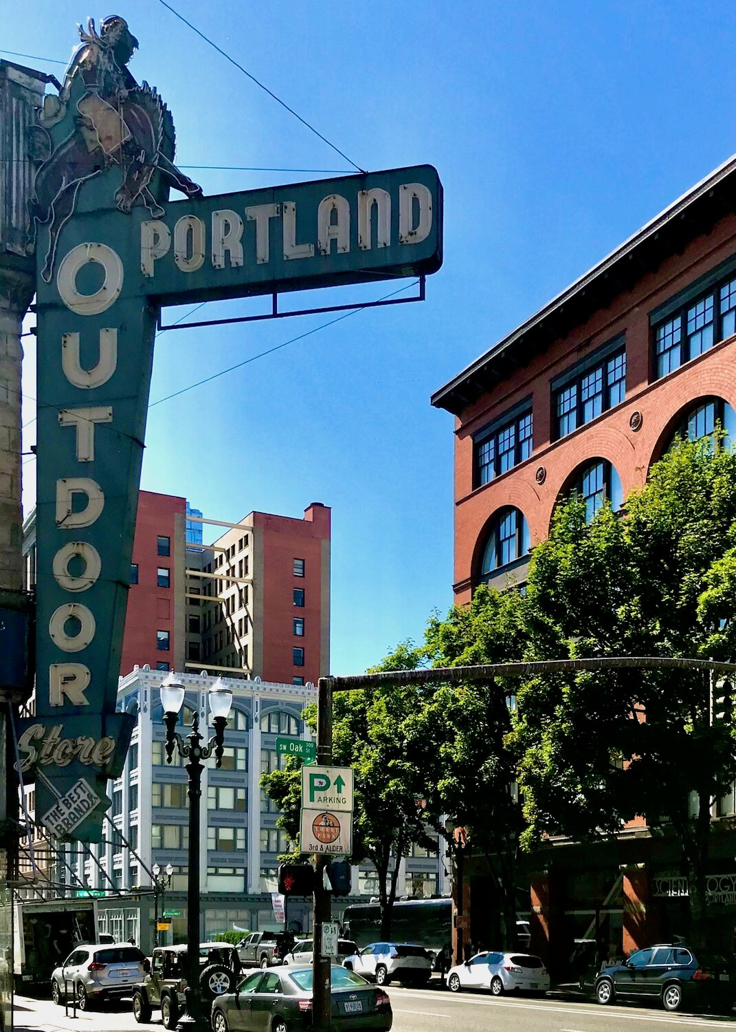 The iconic Portland Outdoor Store in downtown Portland shows off a green retro style neon sign with white lettering while other vintage red brick buildings stand across the street and further down.