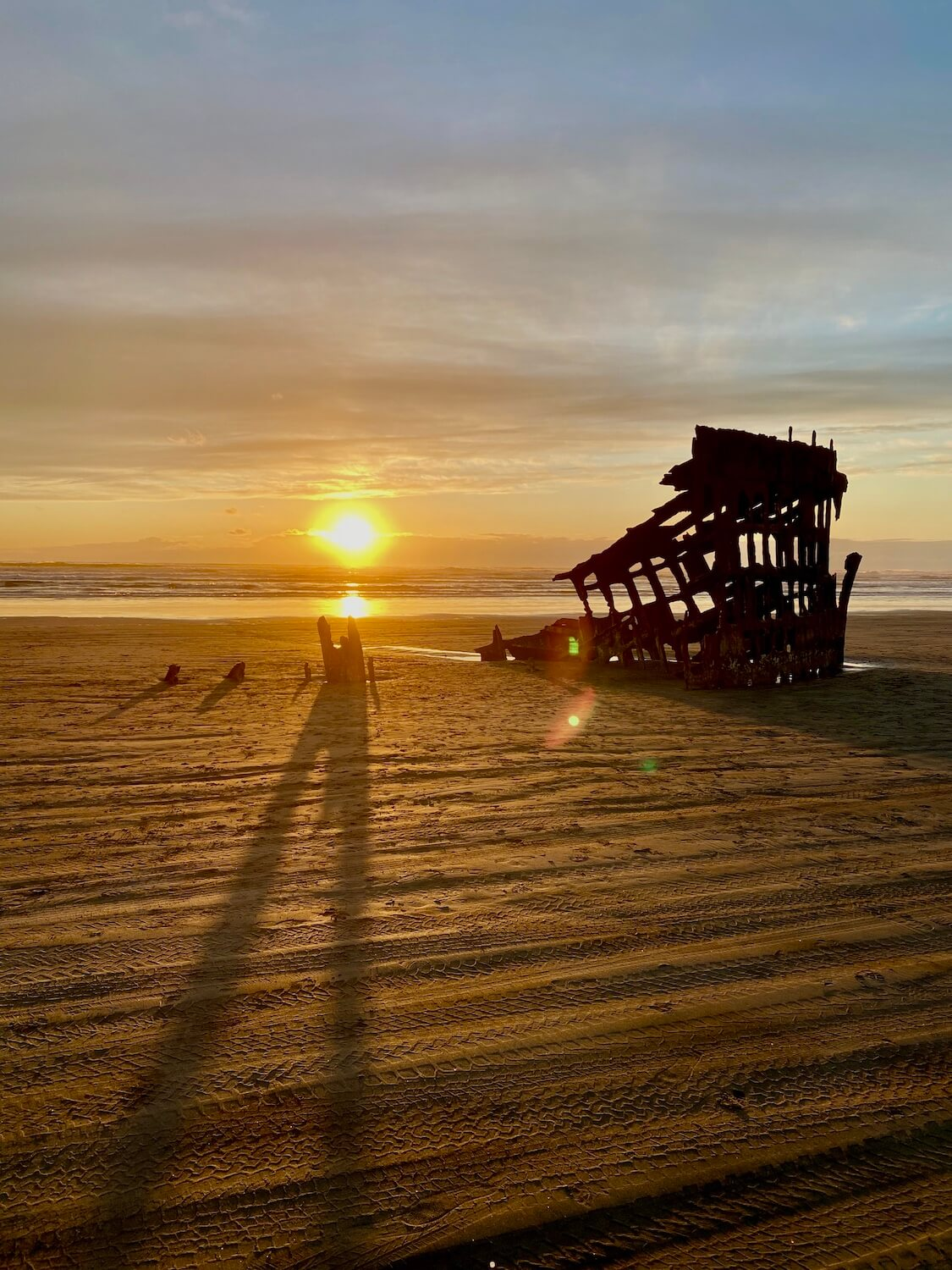 The Peter Irdale shipwreck sits wedged into the sandy beach at Fort Stevens State Park, near Astoria as the sun sets beyond the horizon of the Pacific Ocean. The glow is yellowish as the clouds and upper sky fight to keep their blue color.
