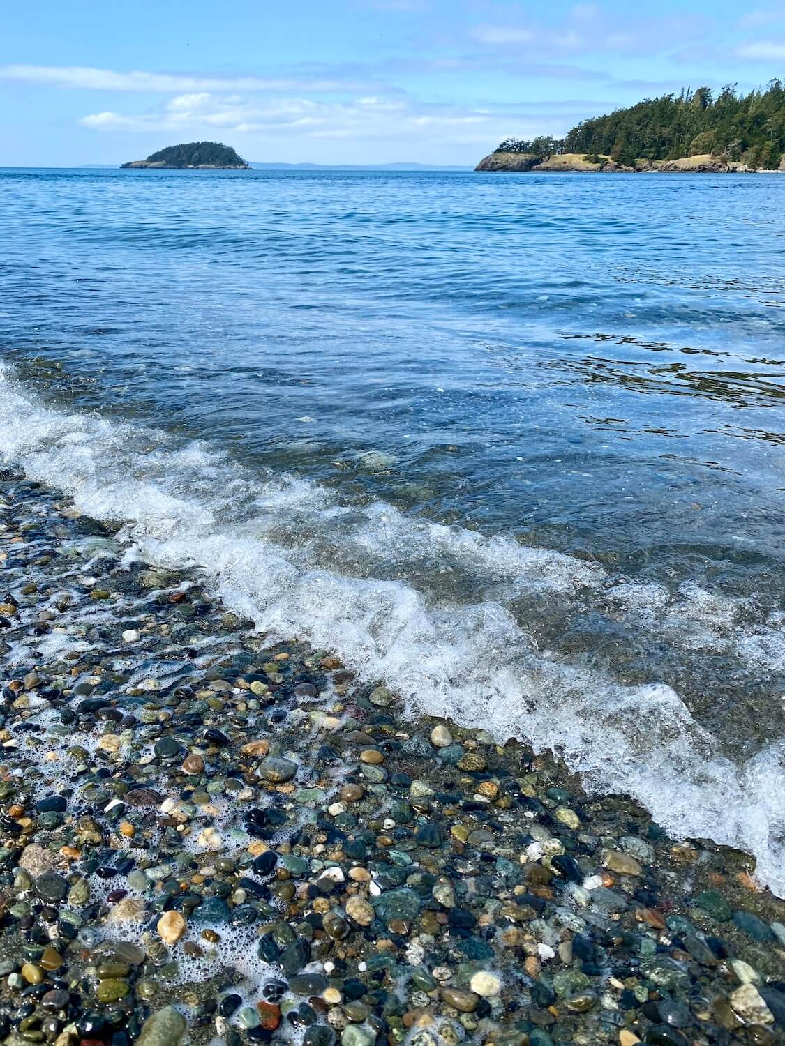 Pacific Northwest travel is all about the water. Here, foamy waves wash up on a pebble beach of the Salish Sea, while islands pop up on the horizon.