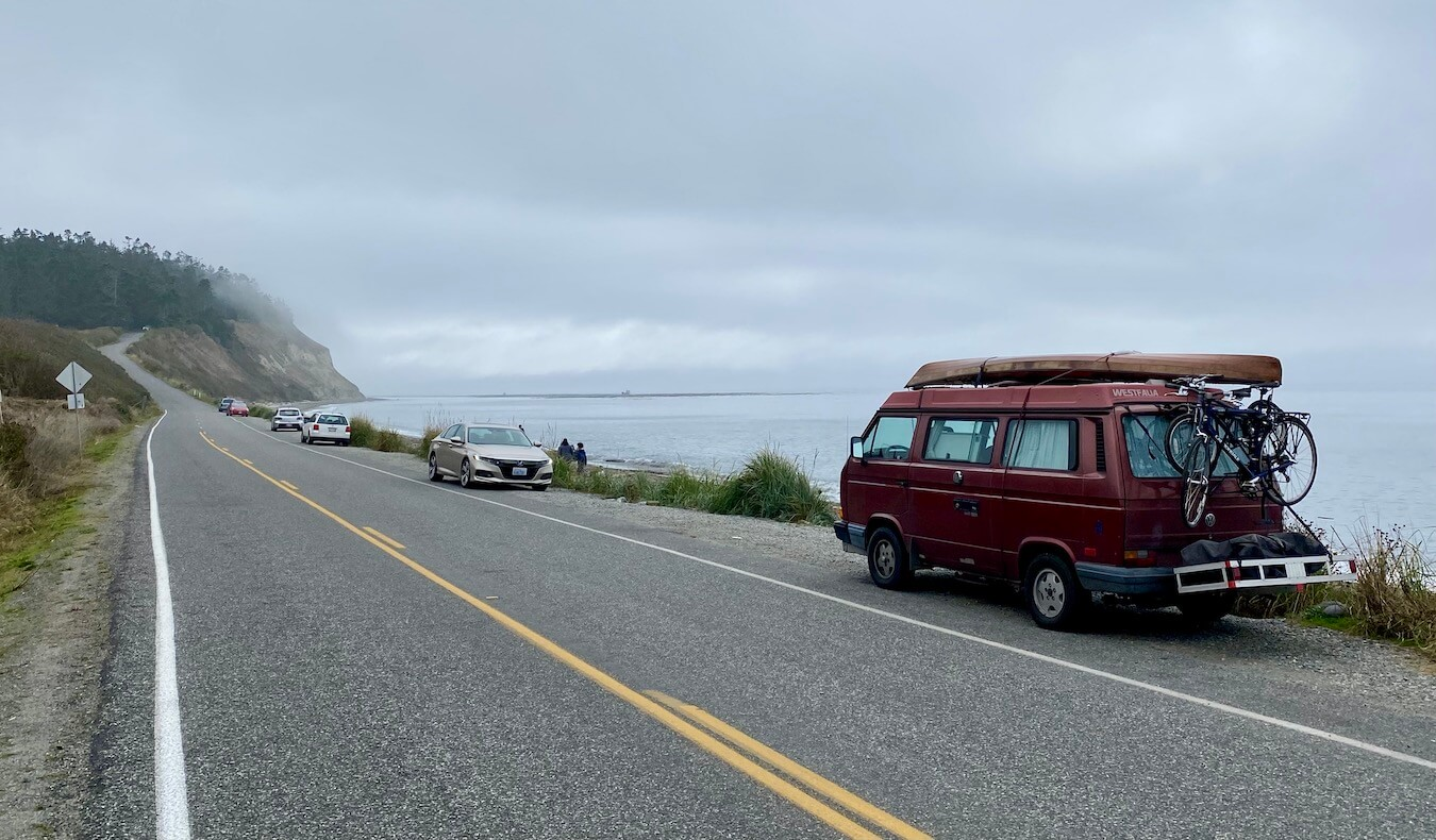 A Volkswagon vanagon with a canoe and bicycles attached to the outside is parked on the side of the road facing the Salish Sea. There are a number of other cars parked on the side as well and the fog begins to roll in in the distance. Water sports are a fun thing to do on Whidbey Island.