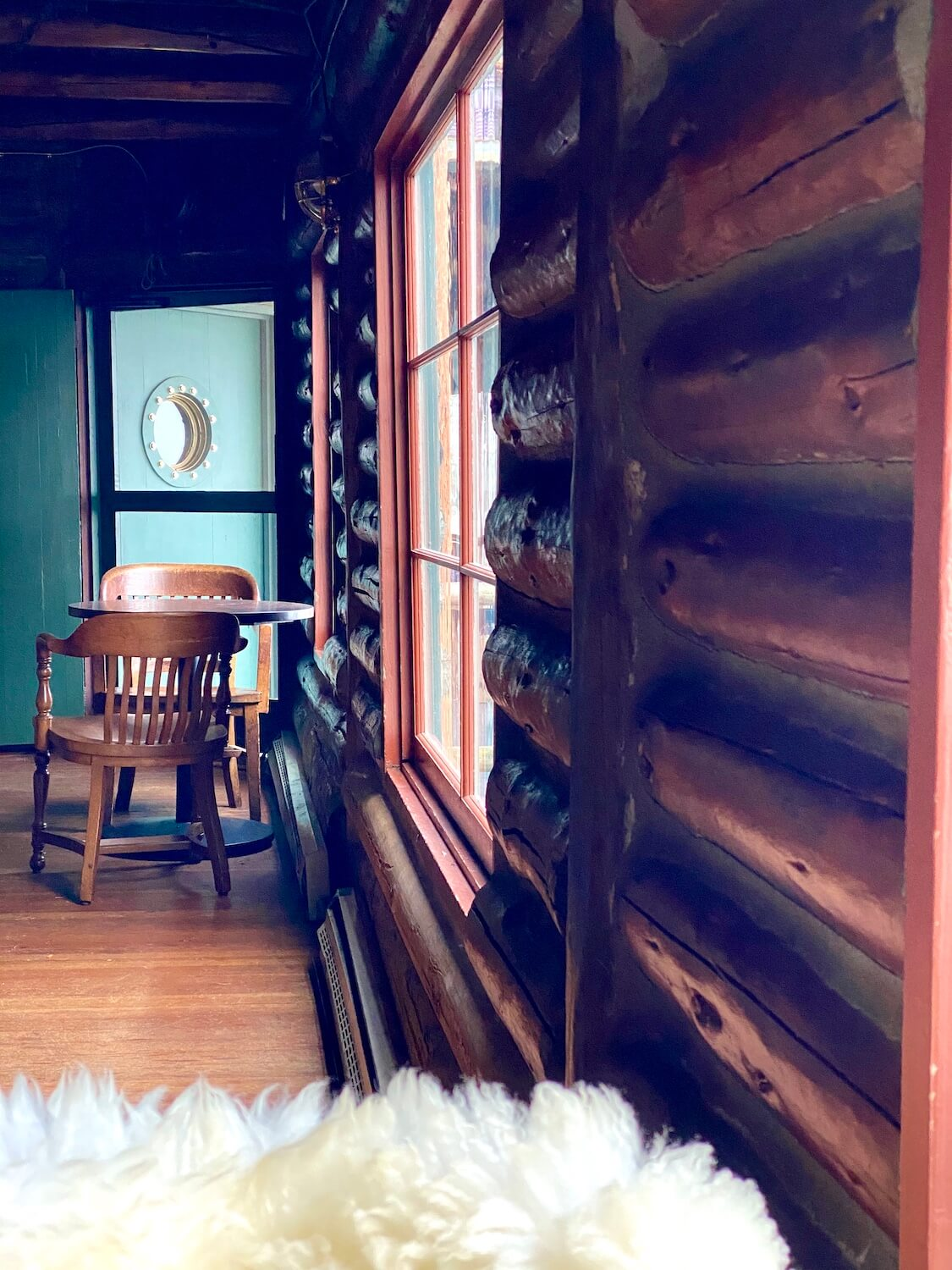 The inside of Captain Whidbey Hotel shows the fluffy white wool blanket draped over a chair while two wooden chairs sit on either side of a wood table, underneath a green door with a porthole. The building is made from logs.