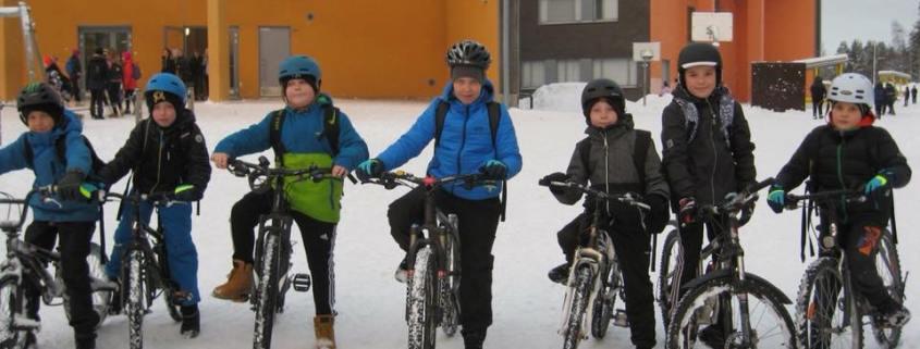 Talvikuva, seitsemän lasta rivissä koulun pihalla, kaikilla pyörät. Keltainen koulurakennus taustalla.