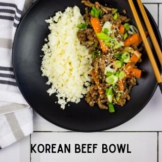 keto Korean Beef Bowl on a black plate with a side of cauliflower rice.