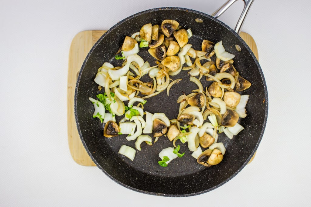 sauteeting the onions and mushrooms in a large black skillet