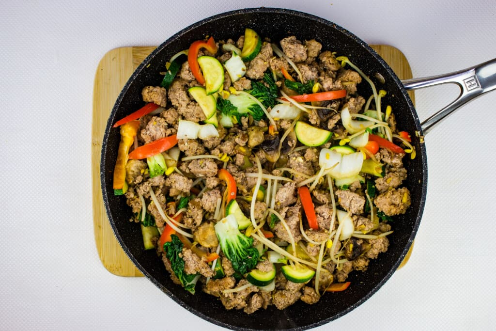 the cooked vegetables and ground pork mixture are in one large skillet