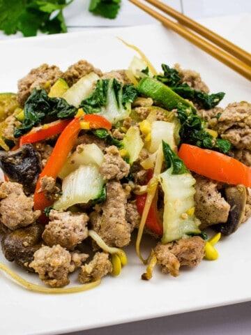 spicy keto pork stir fry on a square plate with chopsticks