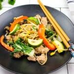 spicy keto pork stir fry with vegetables on a black plate with chopsticks