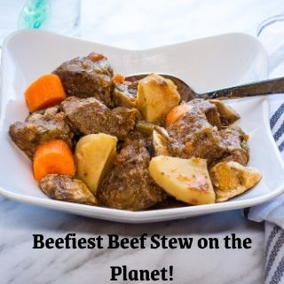 beefiest beef stew on the planet in a bowl with a spoon