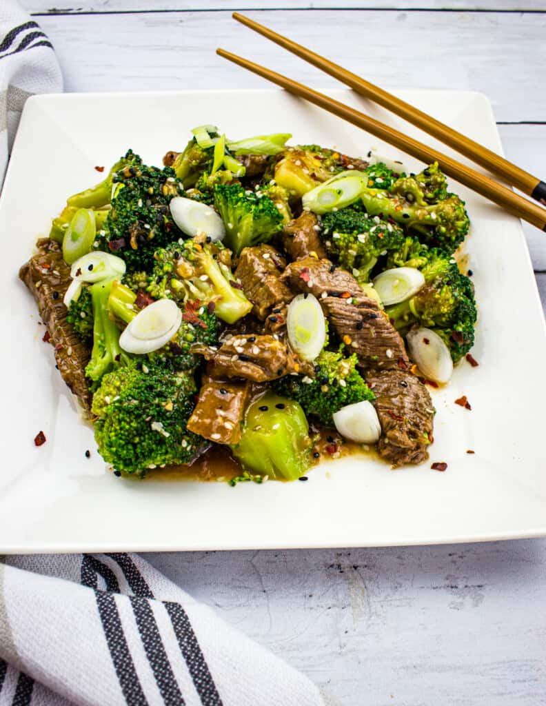 keto beef and broccoli on a square plate with chopsticks