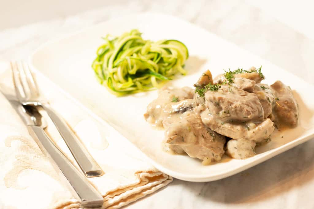 Keto-friendly Pork Stroganoff with Dill served with zucchini spaghetti.