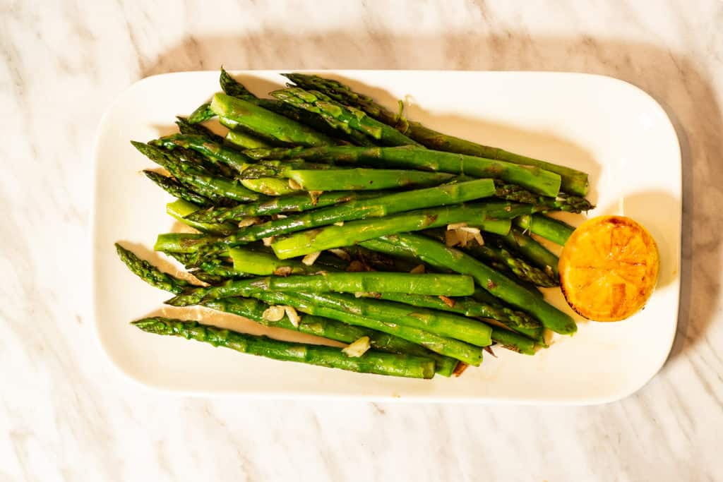 Keto pan-roasted asparagus spears on a plate with caramelized lemon.
