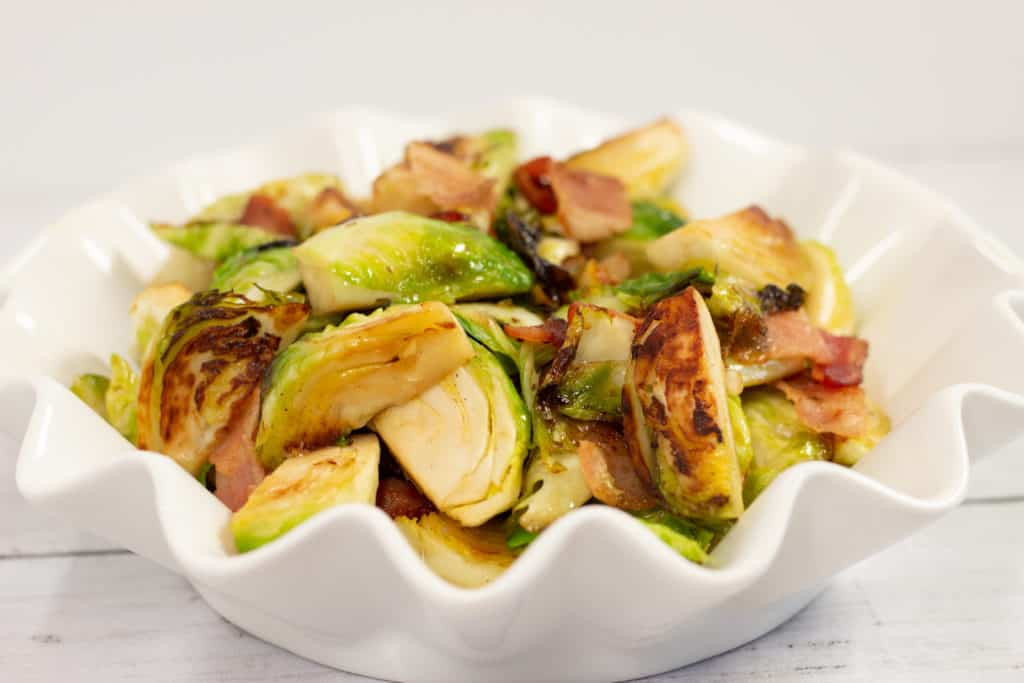 Keto-friendly Brussels sprouts with bacon and maple syrup in a white bowl.