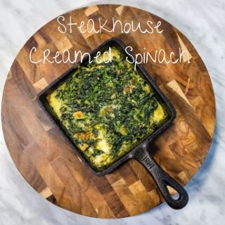 keto steakhouse creamed spinach in a cast iron dish on a wooden board