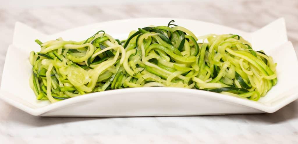 Zucchini noodles in a white dish.