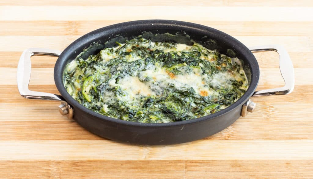 Bubbly and cheesy keto friendly creamed spinach in an oval baking dish
