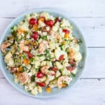 A colorful salad with shrimp, cauliflower and veggies in a lemon dressing
