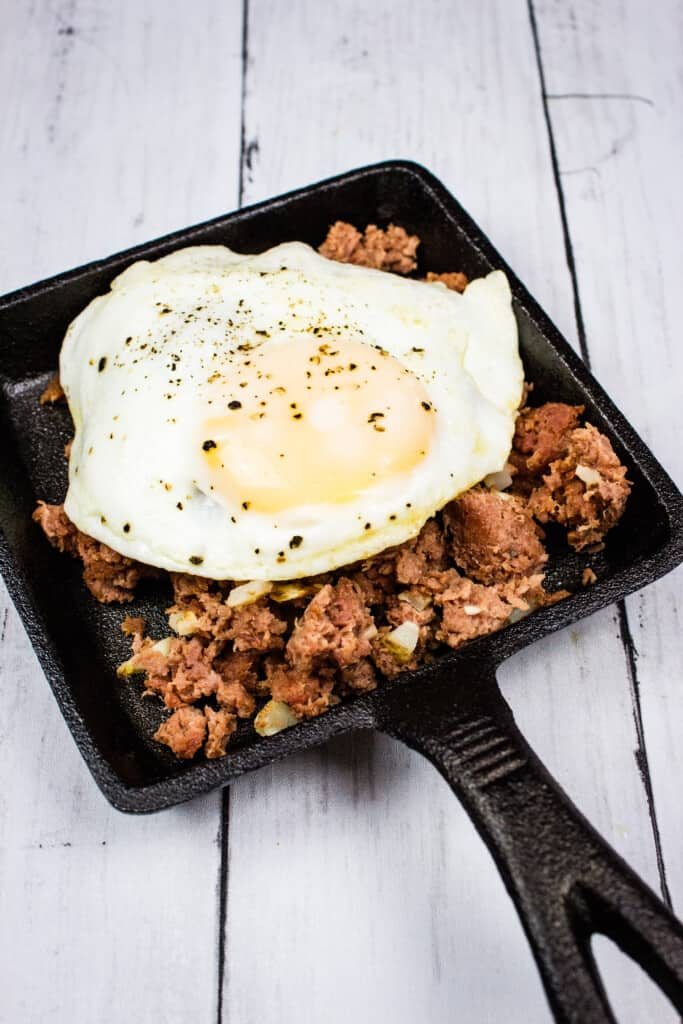 keto corned beef hash on a plate with an egg on top