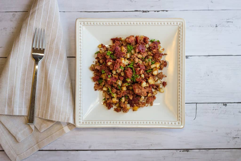 Keto-friendly corned beef hash on a square plate.