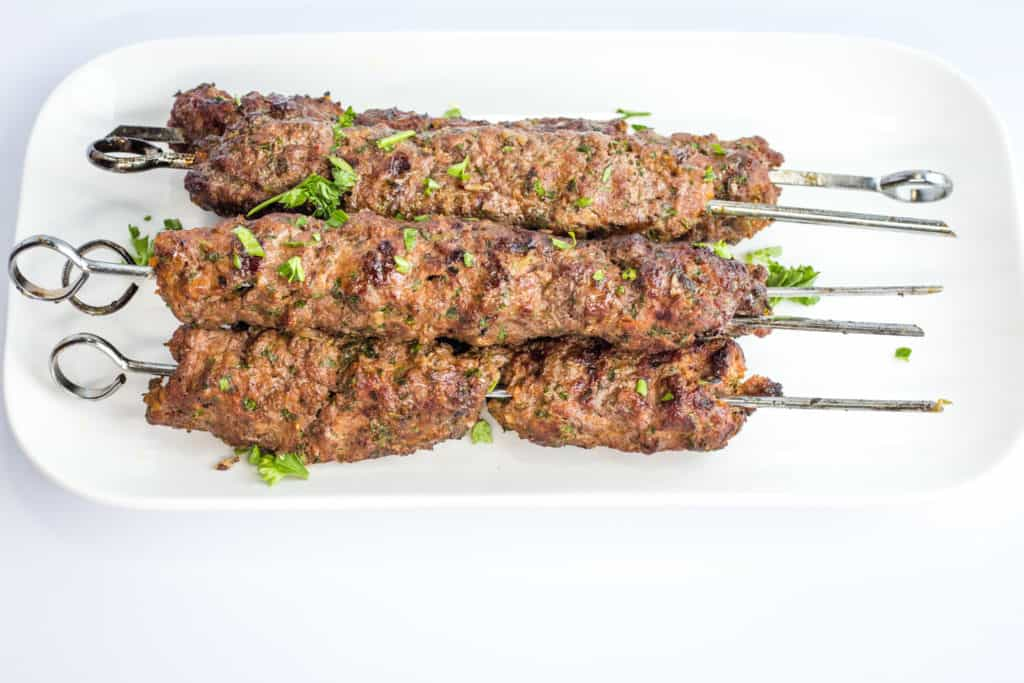 five skewers of grilled low-carb/keto kefta beef kabobs on a white plate
