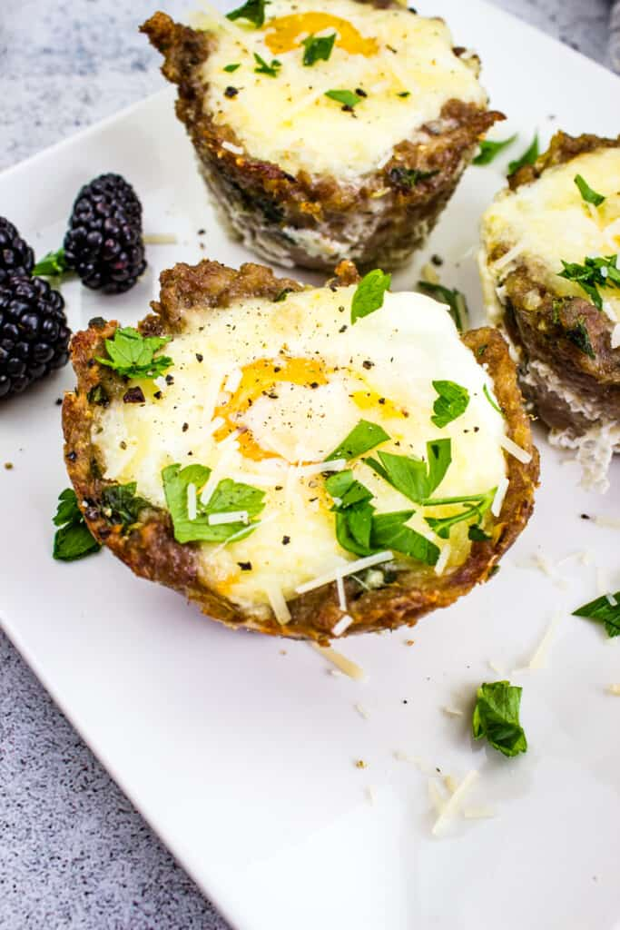keto sausage egg cups on a white plate with blackberries