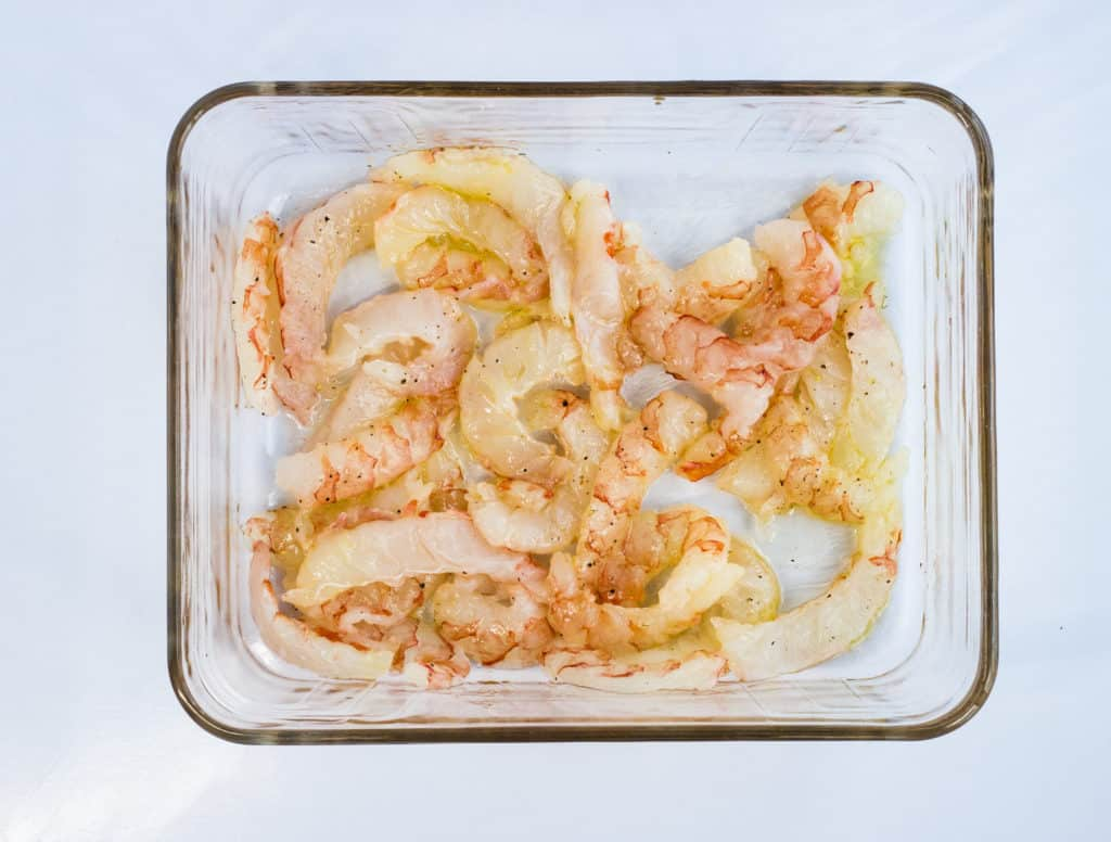 raw shrimp dressed with olive oil, salt and pepper in a glass roasting dish