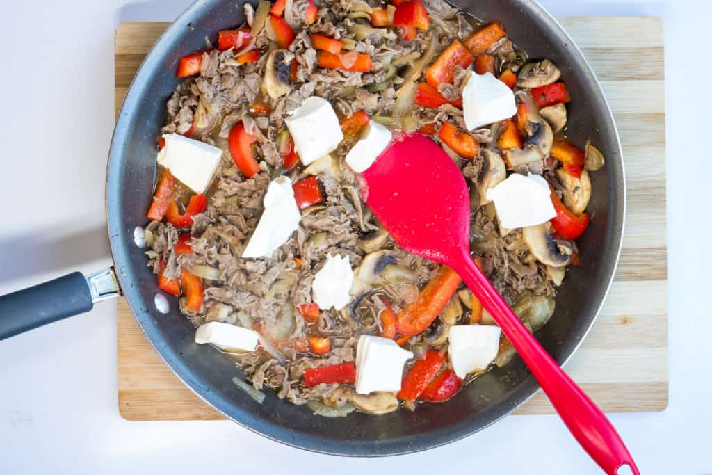 broth and cream cheese added to skillet with beef, mushrooms, onions, and ppepers