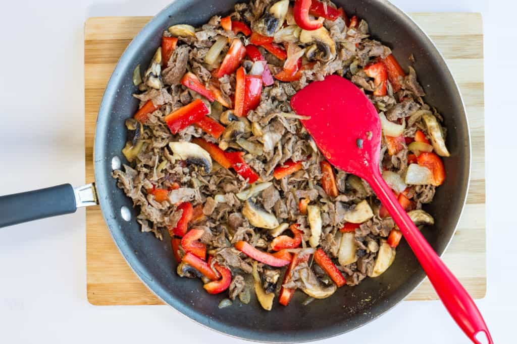 red bell peppers added to cooked beef, onions, and mushrooms in a skillet