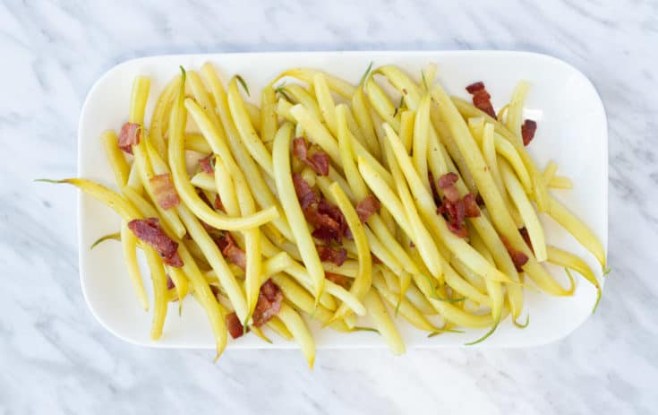 yellow string beans with bacon on a rectangular plate