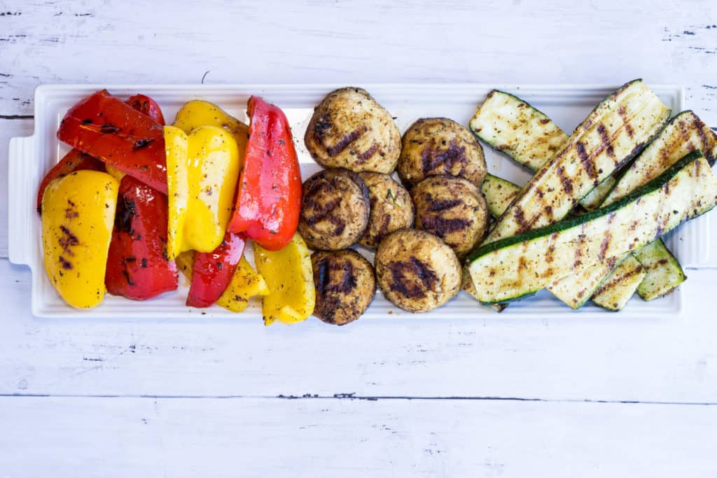 Keto Grilled Veggies with grilled red and yellow peppers, mushrooms, and zucchini on a platter.