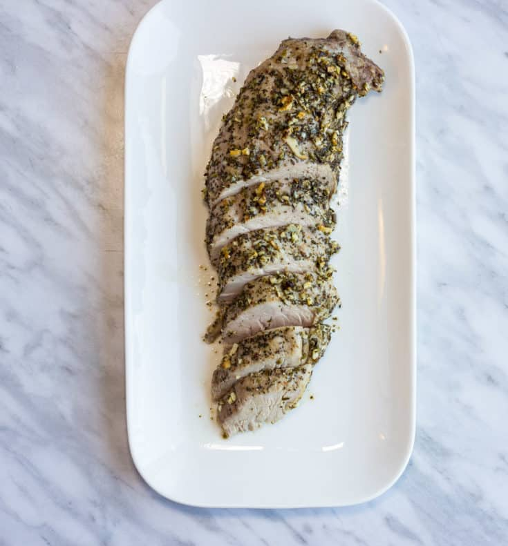 Sliced Garlic & Herb Roasted Pork Tenderloin on a platter.