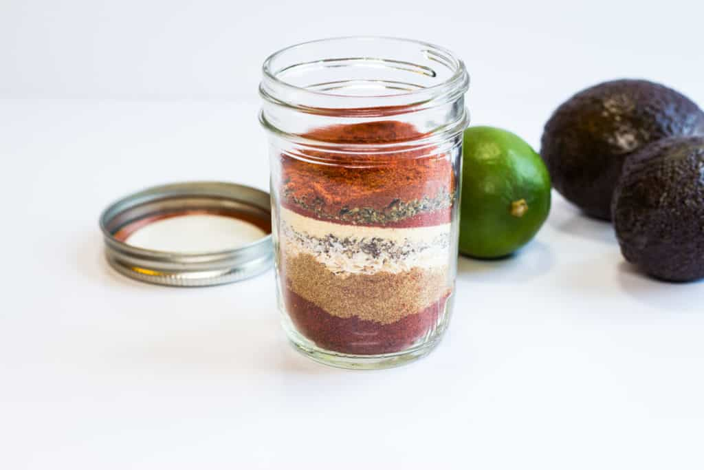 Keto Taco Seasoning in a glass jar with avocado and lime in the background.