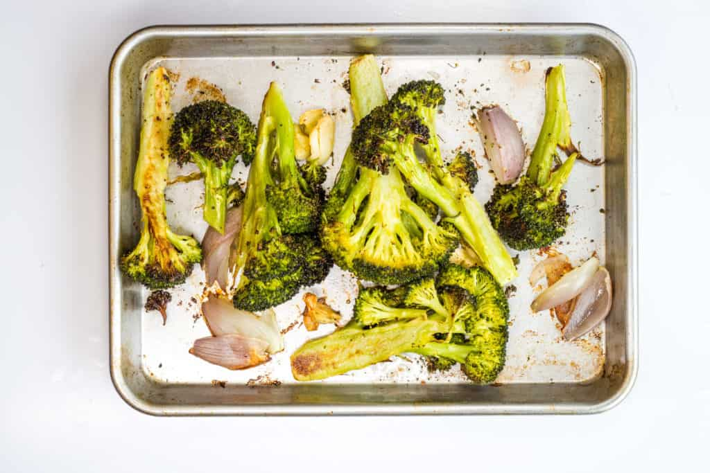 Roasted broccoli, garlic, and shallot on a sheet pan for keto Cream of Roasted Broccoli Soup.