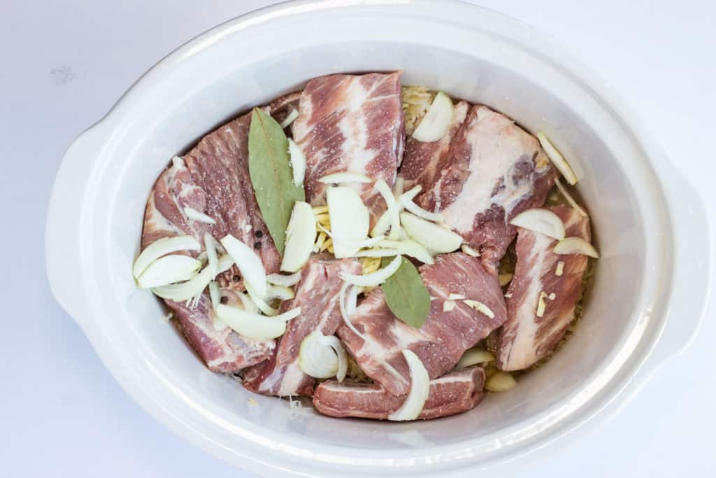 ribs, sauerkraut, bay leaf, onion and garlic in a crock pot ready to cook