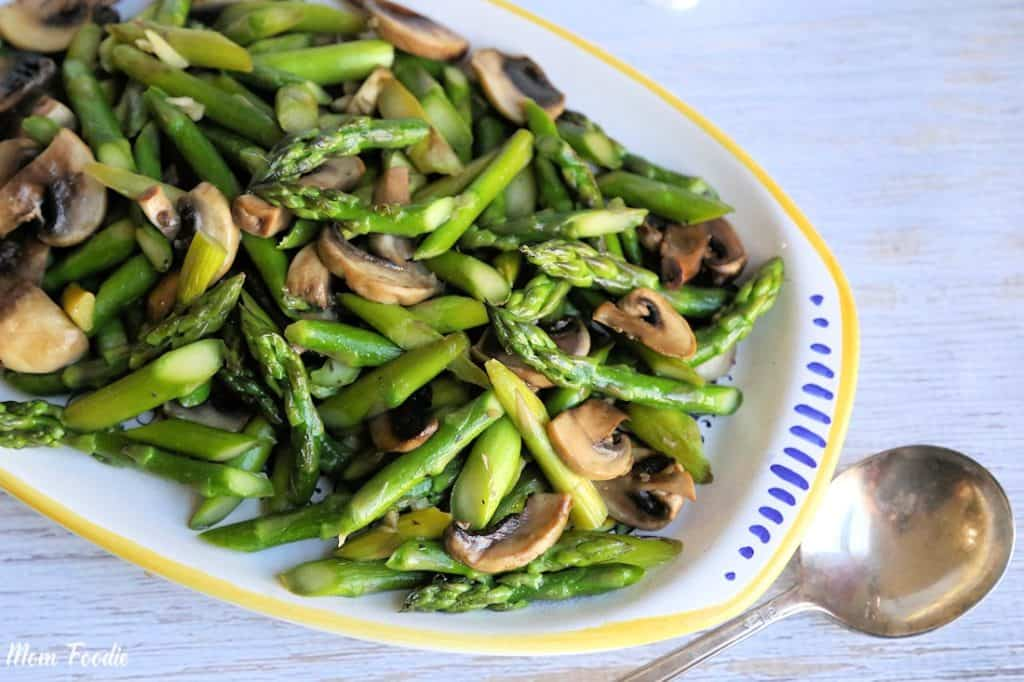 Sauteed Asparagus and Mushrooms in an oval white serving dish with a spoon at the side.