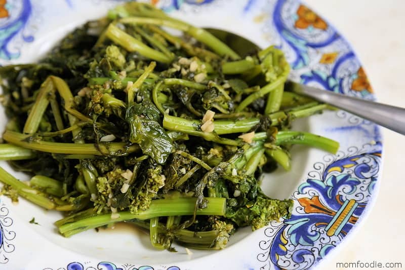 Broccoli Rabe on a blue and white porcelain dish with a spoon.