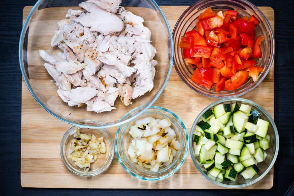 Turkey, pepper, zucchini, onion and garlic prepped in bowls on a cutting board