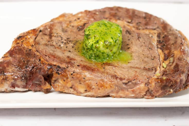 Thick and juicy ribeye steak topped with keto Garlic & Herb Butter Bomb.